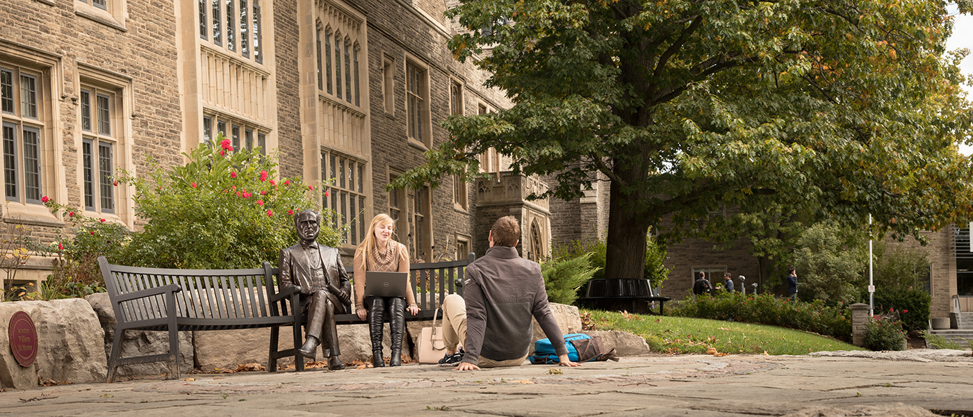 Photo of Students sitting beside William McMaster Sculpture